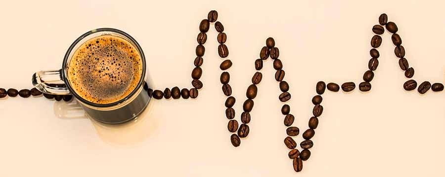 taza de café y granos de café dibujando un electrocardiograma