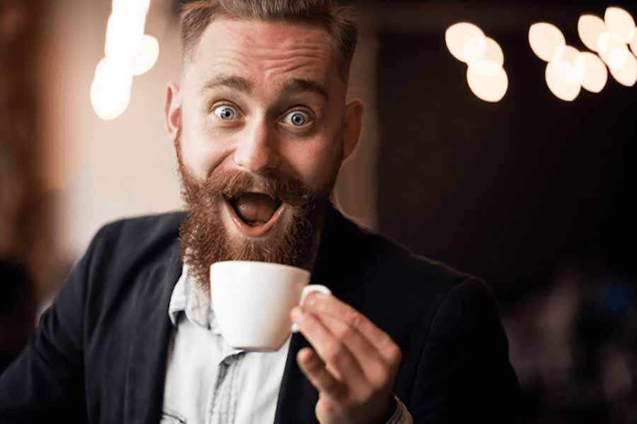 hombre con mucha barba y bigote toma cafe muy contento