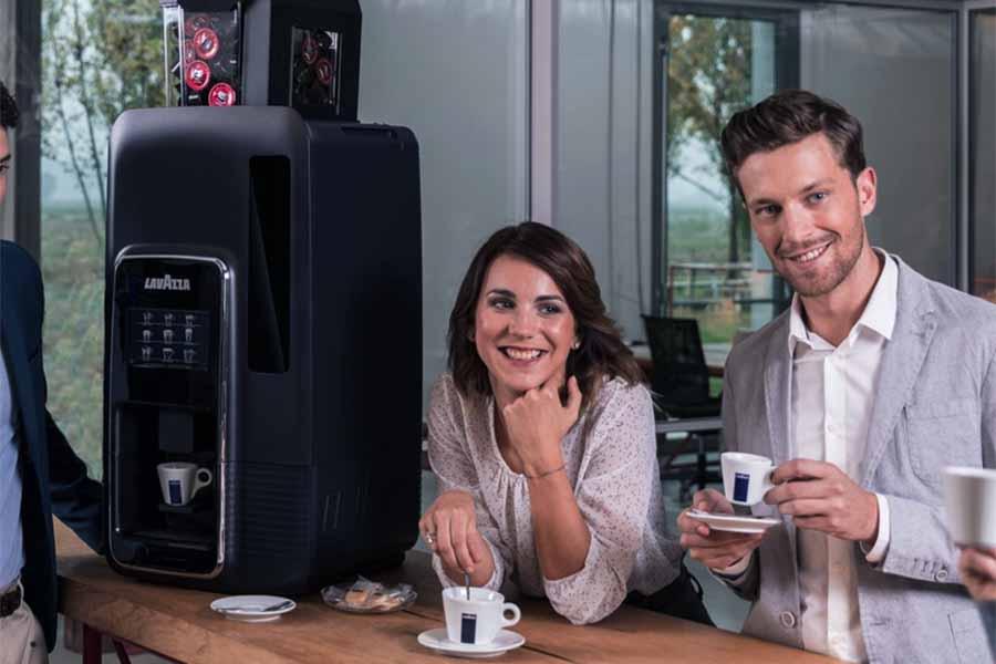 maquina de cafe lavazza y hombre y mujer toman cafe en la ofcina