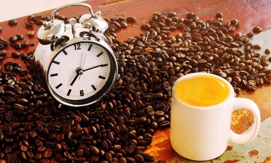 despertador blanco encima de granos de cafe y taza con cafe