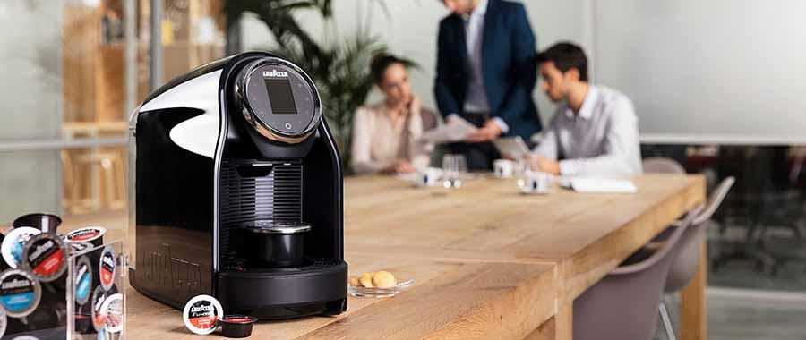 maquina de capsulas de cafe lavazza encima de una mesa en sala de reuniones de una empresa