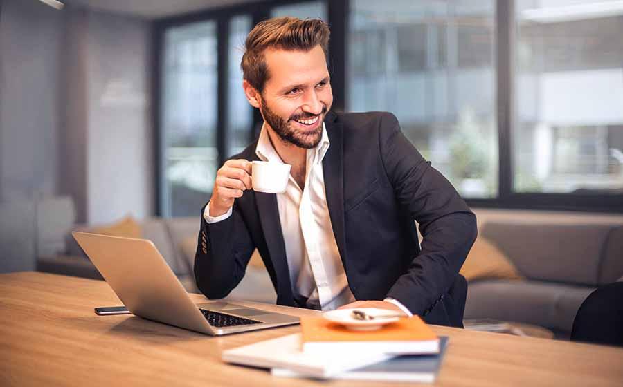 hombre sonrie tomando cafe oficina con ordenador y libros encima de mesa